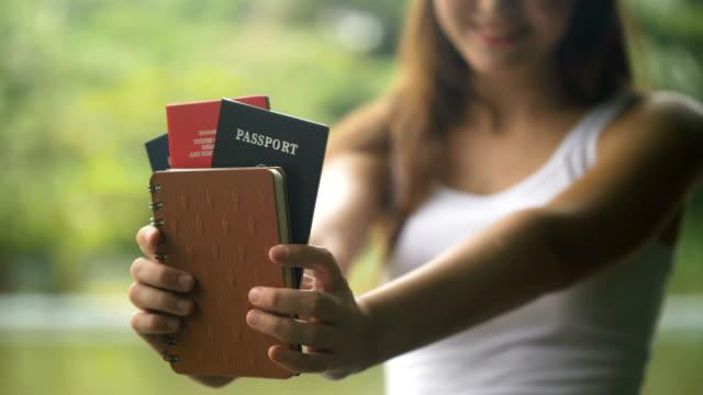 若い白人女性が笑顔を笑顔と航空券とパスポートを保持して - パスポート点の映像素材/bロール
