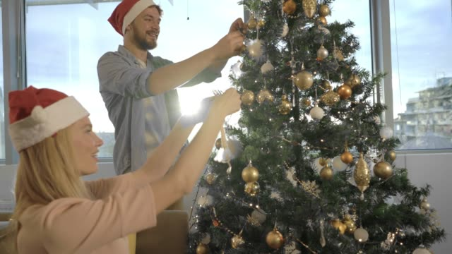 young smiling couple decorating christmas tree together at their apartment. - decorating the christmas tree stock videos & royalty-free footage