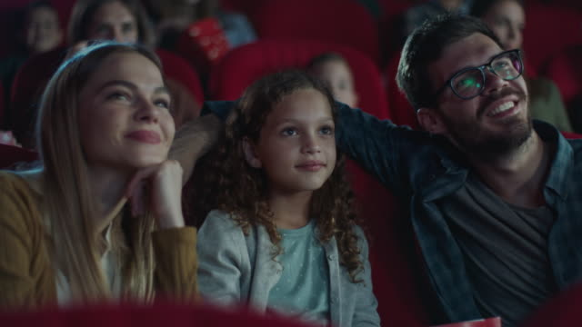 young smiling family with child in cinema - recreational pursuit stock videos & royalty-free footage