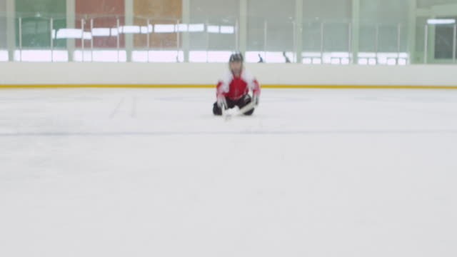 ms young smiling female hockey player skating on ice rink sliding on stomach - hockey glove stock videos & royalty-free footage