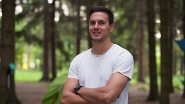 junger lächelnder mann auf dem campingplatz - arme verschränkt stock-videos und b-roll-filmmaterial