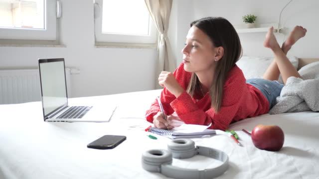 vídeos y material grabado en eventos de stock de joven estudiante sonriente usando computadora portátil para aprender en casa - estudio habitación