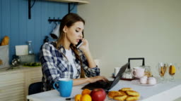 Young smiling woman browsing social media using laptop computer and talking phone during breakfast in the morning