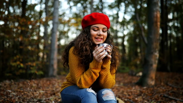 Young smiling woman enjoying in hot drink at forest