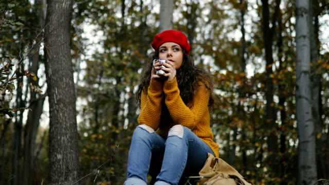 vídeos de stock e filmes b-roll de young smiling woman enjoying in hot drink at forest - fazer uma pausa