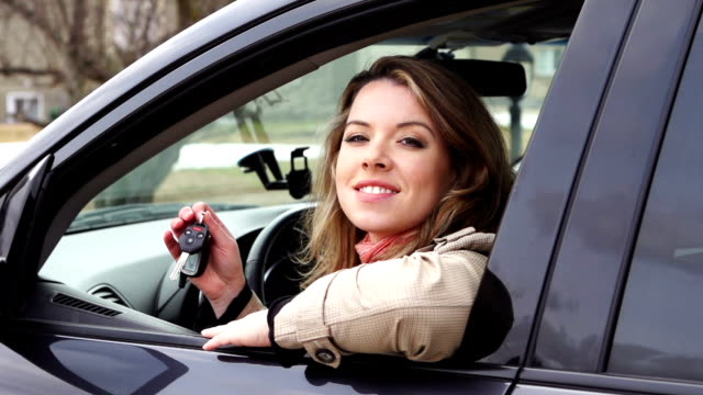Jeune femme souriante avec clé