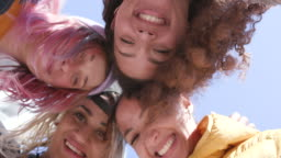 4 young smiling women in a group - heads together shot from below