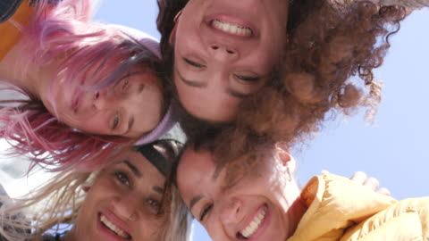 4 young smiling women in a group - heads together shot from below - focus concept stock videos & royalty-free footage