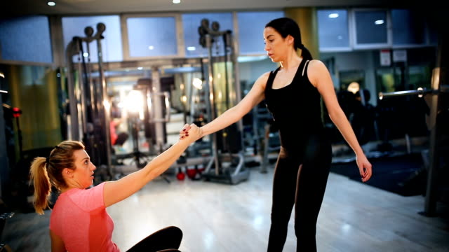 young smiling women stretching together while holding hands - strongwoman stock videos & royalty-free footage