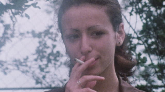 1978 montage young smoker smoking, watching himself in a mirror, and coughing, and a more sophisticated smoker smoking outdoors / united kingdom - smoking stock-videos und b-roll-filmmaterial