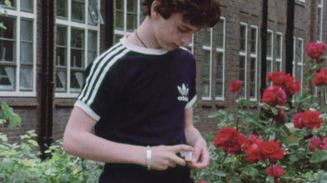 1978 montage young smoker walking then lighting a cigarette outside a school / united kingdom - 1978 stock videos and b-roll footage
