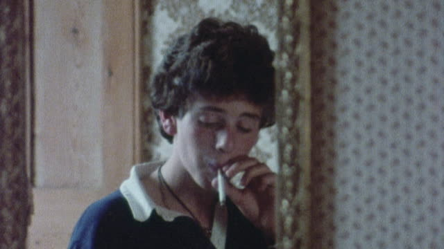vídeos de stock, filmes e b-roll de 1978 cu a young smoker watching himself in a mirror / united kingdom - tossindo