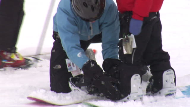 slo mo, cu, tu, young snowboarder fastening boy's (6-7) boot on slope, whitefish, montana, usa - attività del fine settimana video stock e b–roll