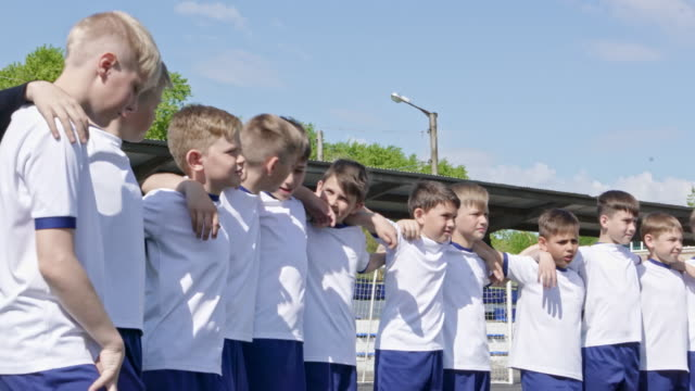 Young soccer athletes embracing on stadium field