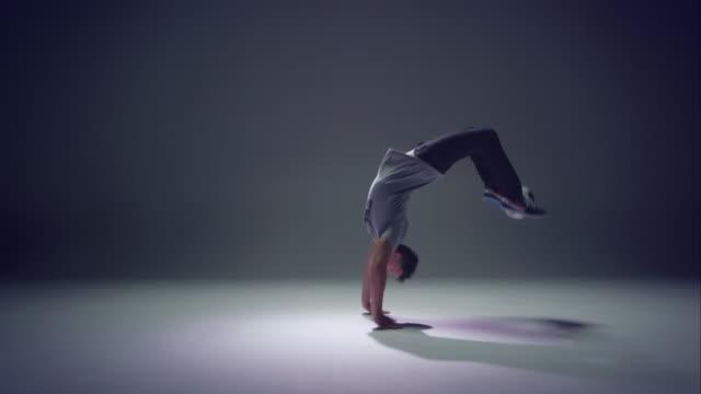 giovane facendo un calcio freestyler fare le capriole all'indietro con una palla - attività acrobatica video stock e b–roll