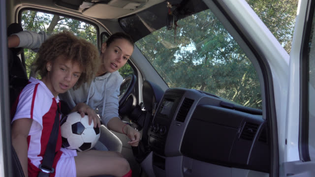 young soccer mom picking up kids for soccer practice in a mini van - drive ball sports stock videos & royalty-free footage
