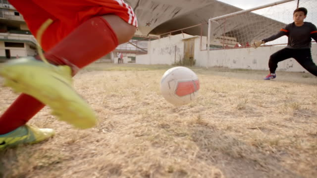 Young soccer player dribbles down field and kicks ball between goalie's hands to score goal