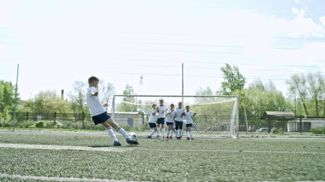 Young soccer player performing free kick