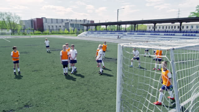 Young soccer player scoring a goal with head
