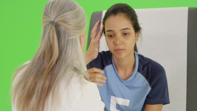 vídeos de stock, filmes e b-roll de a young soccer player with a head injury on green screen - physical injury