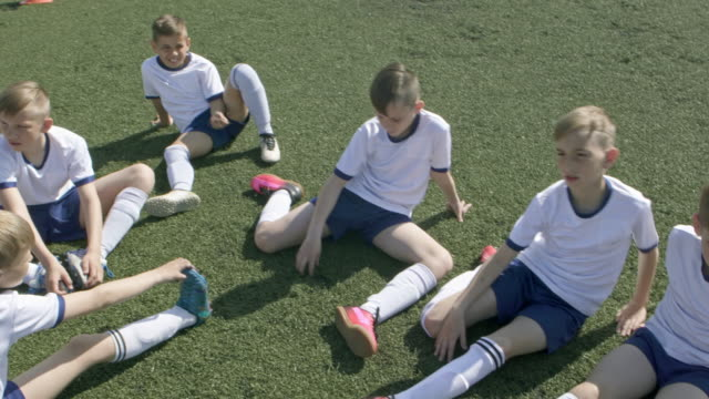 young soccer players stretching on green field - football team stock videos & royalty-free footage