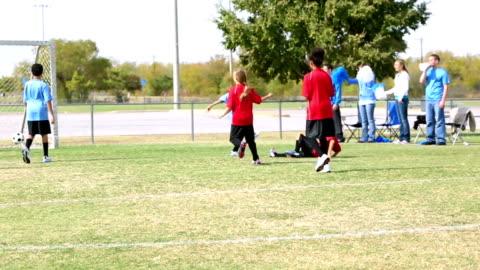 vídeos y material grabado en eventos de stock de joven equipo de fútbol hacer un gol y celebrar - portería artículos deportivos