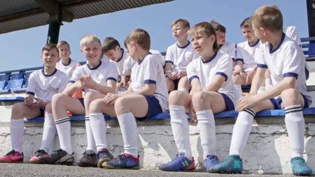 Young soccer team sitting on bleacher in stadium at summer day