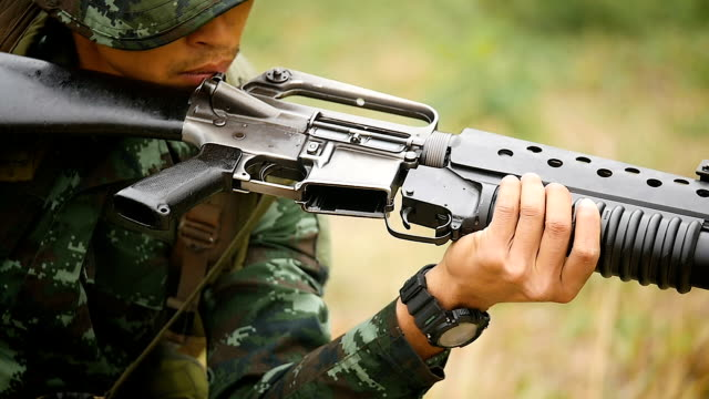 Young soldiers changing bullets in the magazine to shot the firing action, Army soldiers with guns during the military operation, War concept