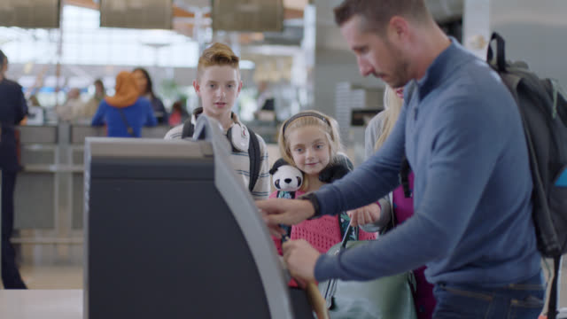 young son and daughter watch as father hurriedly checks in using kiosk at ticket counter in airport. - ticket counter stock videos & royalty-free footage