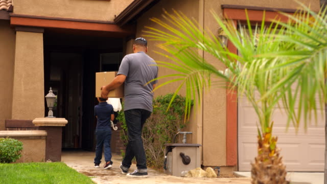 ms young son helping father move items from moving truck into new house - genderblend stock videos & royalty-free footage