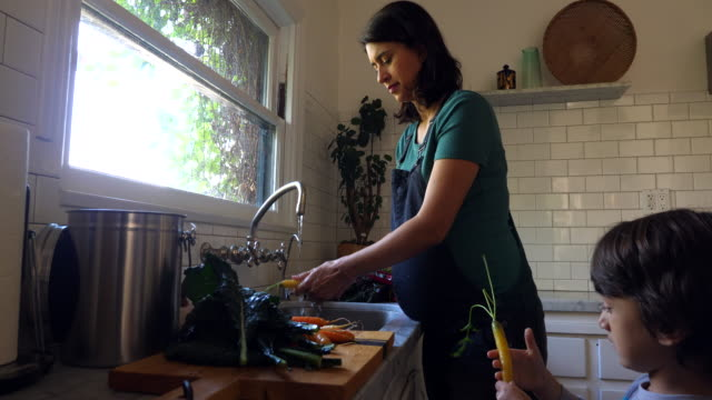 cu young son helping pregnant mother wash organic vegetables at sink in kitchen - hygiene stock videos & royalty-free footage