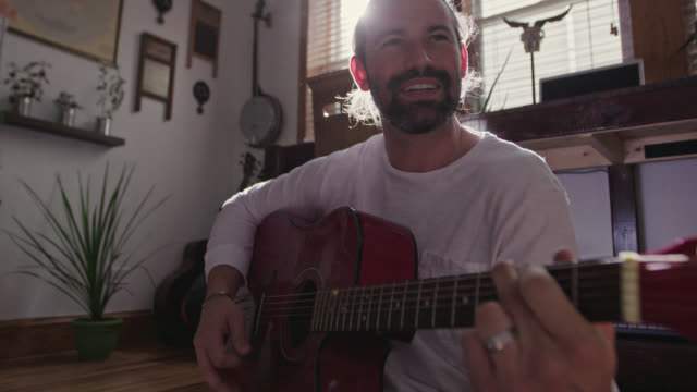MS SLO MO. Young songwriter smiles as he plays acoustic guitar and sings in sunny apartment.