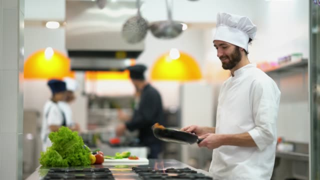 young sous chef preparing some vegetables on a frying pan looking focused but happy - commercial kitchen stock videos & royalty-free footage