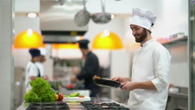 vídeos y material grabado en eventos de stock de preparación de algunas verduras en una sartén mirando al joven sous chef centrado pero feliz - chef