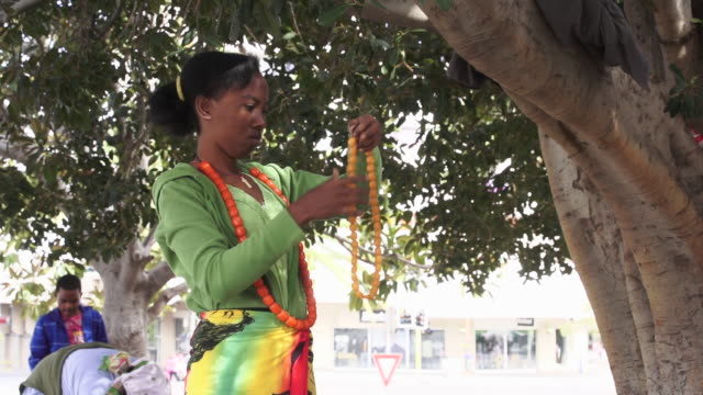MS TD TU Young south African teenage girl hands beads from tree for sale / Windhoek, Khomas, Namibia