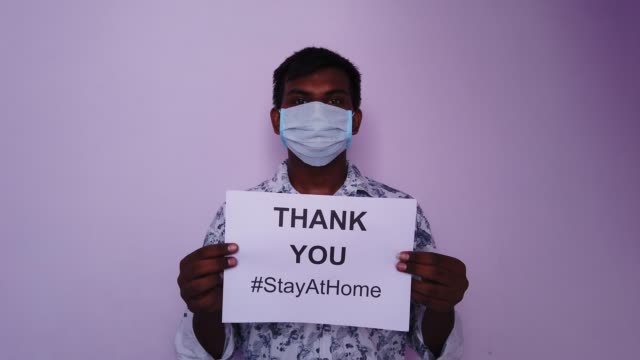 young south asian man holding a sign board printout on paper saying- thank you #stayathome - placard stock videos & royalty-free footage