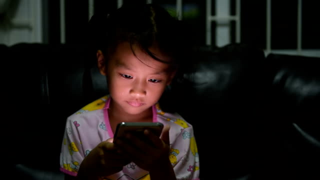 südostasiatischer mädchen spielen elektronischer spiele auf smartphone - neugierde stock-videos und b-roll-filmmaterial