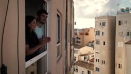 Young spanish couple giving an applause to all sanitary staff and kissing from her apartment window during quarantine from COVID 19 in Mallorca, Spain