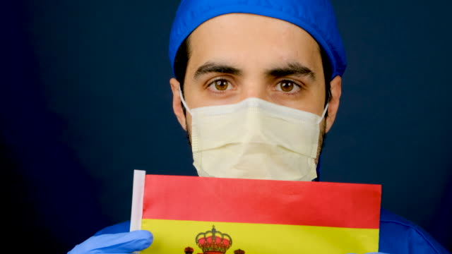 外科用マスクと保護眼鏡を取り外す若いスペインの男性医療従事者 - スペイン国旗点の映像素材/bロール