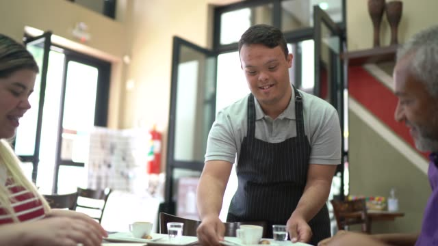 junge spezialbedürfnisse kellner serviert kaffee an kunden in einem café - employee engagement stock-videos und b-roll-filmmaterial