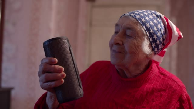 young spirit behind a wrinkled face. american patriotism. close-up portrait of a beautiful cheerful grandmother opening her christmas present and listening to music. - one mature woman only stock videos & royalty-free footage