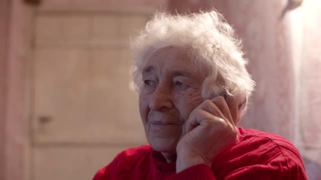 junger geist hinter einem zerknitterten gesicht. weisheit und glück. close-up portrait einer schönen fröhlichen großmutter am telefon mit ihrer familie. - einsamkeit stock-videos und b-roll-filmmaterial