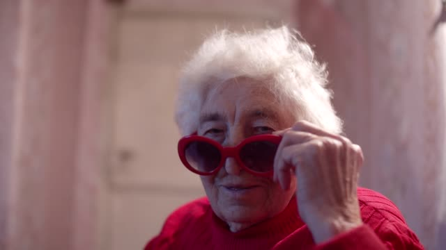 young spirit behind a wrinkled face. wisdom and happiness. close-up portrait of a beautiful cheerful grandmother smiling and winking. - sunglasses stock videos & royalty-free footage
