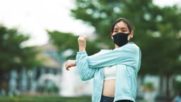 Young Sport woman stretching before a run outdoors With Face Mask