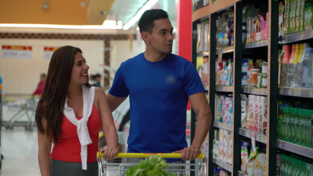 young sports couple shopping for groceries at the supermarket pushing cart while talking - sportswear stock videos & royalty-free footage