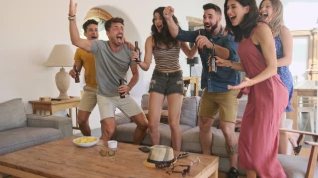 若いスポーツファンがテレビでビールと応援チームを楽しむ - living room点の映像素材/bロール