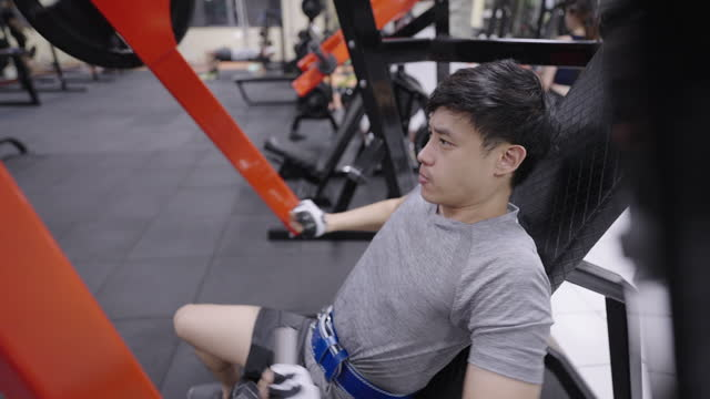young sportsman doing arm and shoulder exercise on seated machine in gym. - human limb stock videos & royalty-free footage
