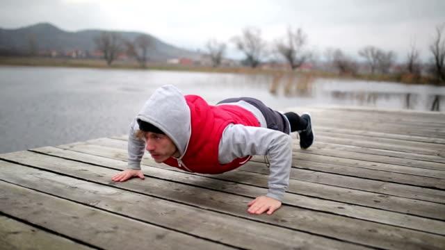 vídeos de stock e filmes b-roll de young sportsman doing pushups - flexionar los músculos