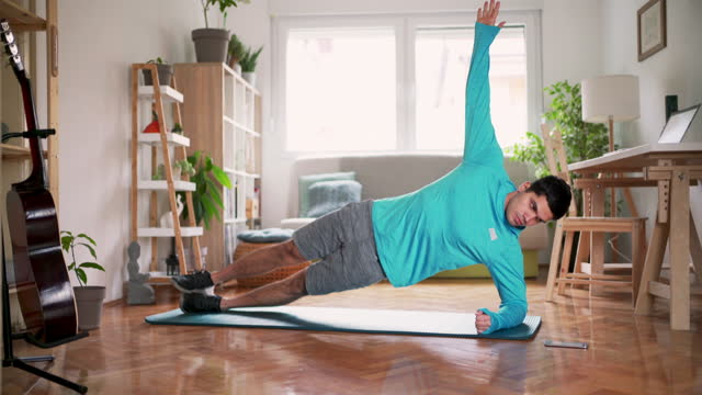young sportsman doing side plank exercise at home - stretching stock videos & royalty-free footage