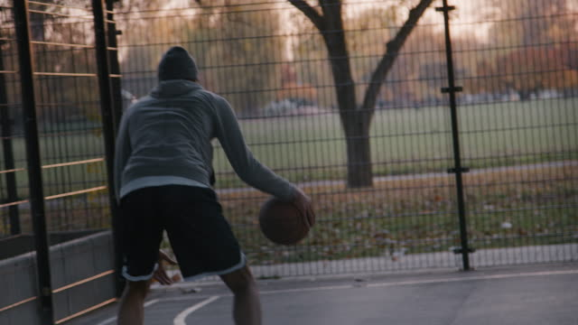 young sportsman dribbling ball on basketball court - bouncing stock videos & royalty-free footage